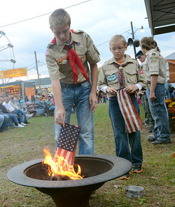 Brothers, Dalton, left, and Dylan Klinger of McClure add flags to the fire Friday Sept. 21, 2012 during the flag retiring ceremony at the Beaver Community Fair.