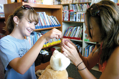 """Moriah Cross, 12 Beaver Springs and Leah Cross, 14 Beaver Springs thread a needle together during the """"Frankentoys"""" program at the Beavertown Library."""