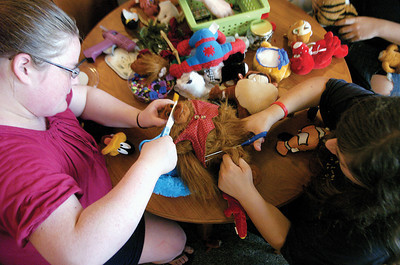 "Kaitlyn Royer, 15 McClure, and Amanda Stauffer, 14 Beavertown cut apart a stuffed animal during the ""Frankentoys"" program at the Beavertown Library."