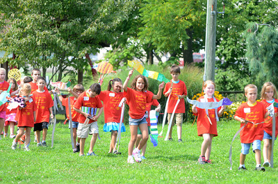 A parade of kids walk into the start of a play put on at the Kidsgrove art camp in Selinsgrove on Friday.