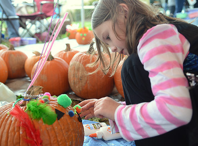 Mackenzie Fletcher, 6 of Selinsgrove, decorates a pumpkin at the Kidsgrove Fall Festival on Saturday afternoon in Selinsgrove.