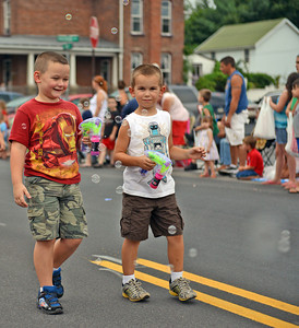 Amanda August/For The Daily Item Mason Bielski, 6, and Landon Herman, 6, both of Selinsgrove, use bubble machines while walking in the Middleburg Fireman's Carnival parade on Thursday night. The boys were walking with the Snyder Union Mifflin Child Development Inc., which was one of about 30 floats in the parade.