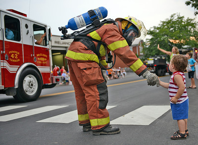 Amanda August/For The Daily Item McClure Volunteer Fire Company firefighter Keith Maltin shakes the hand of Colin Brandt, 2 of Middleburg, during the Middleburg Fireman's Carnival parade on Thursday night.
