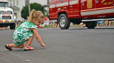 Amanda August/For The Daily Item Peyton Yerger, 2 of Middleburg, picks up candy thrown by one of the firetrucks in the Middleburg Fireman's Carnival parade on Thursday night. There were about 13 fire companies in the parade, along with three privately owned firetrucks.