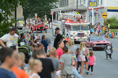 Fire trucks and other vehicles make their way down Main Street past thousands of people out to see the Middleburg Fireman's Parade on Thursday evening.