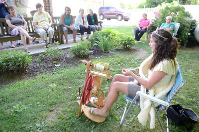 Ashley Shaw, right, the reigning PA Lamb and Wool Queen, demonstrates the art of spinning to people at the Penns Creek Adult Resource Center on Monday.