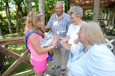 Madison Shaw, 12, left, Harrisburg, holds a Angora rabbit named Mouse for Galen Keister, Penns Creek, Phyllis Moyer, Penns Creek, and Dianna Hassinger, Beavertown, to pet on Monday at the Penns Creek Adult Resource Center as she and her older sister Ashley Shaw, the 2013 PA Lamb and Wool Queen, paid a visit to the center.