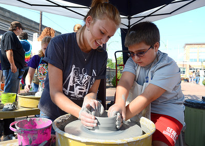 Cristi Beeler, art teacher at Selinsgrove High School, helps Cameron Fogarty, 9, of Selinsgrove sculpt a bowl at the National Art Honor Society's booth Saturday during the 34th Annual Market Street Festival in Selinsgrove Sept. 22, 2012.