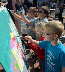 Logan Othoudt, 7, from back, Cameron Fogarty, 9, Camryn Bogush, 4, and Alex Bogush, 5, add their marks Saturday to the community painting during the 34th Annual Market Street Festival in Selinsgrove Saturday Sept. 22, 2012. The painting along with the names of all the children who helped will be hung at the Selinsgrove Community Library.