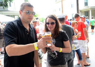 Tom and Gina Miller of Frackville, Pa. grab a sample of a beer from Magic Hat Brewing Company during Selinsgrove's brewfest Saturday July 21, 2012.