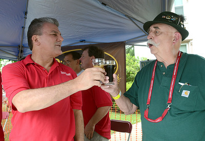 Ernie Kemper, a brewer with River House Brew Pub in Lewisburg, shares a toast with Roger Klinger of Millersburg Saturday during the annual Selinsgrove Brewfest.