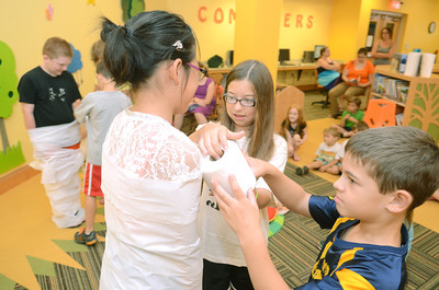 Nina Yang, 10, left, gets wrapped up like a mummy by Laura Malehorn, 10, and Camden Smith, 7, as part of a Egyptian themed lesson at the Selinsgrove Library on Monday morning as part of their summer reading program.