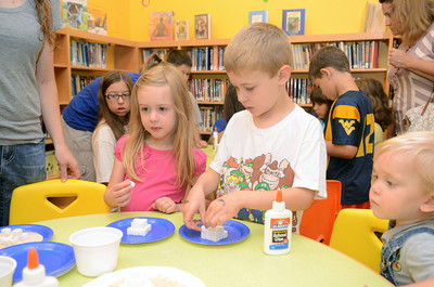 Talia Mowery, 4, left, and her brother Ryan, 6, make sugar cube pyramids at the Selinsgrove Library on Monday morning as part of their summer reading program.