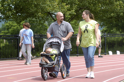 Joe and Leah Auker of Mount Pleasan Mills push their son Mitch, 3, around the track at Susquehanna University during the Selinsgrove Relay For Life on Friday.