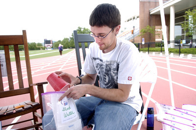 Adam Culp of Mifflinburg puts sand in the bottom of luminary bags at the Selinsgrove Relay For Life on Friday.