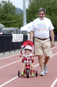 Steve Rauch, Selinsgrove, pushes his granddaughter Hannah Rauch, 1, Middleburg, around during Selinsgrove's Relay For Life on Friday.