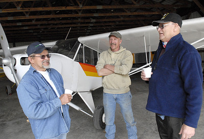 Harold Snook, left, chats with fellow aviation fans, Carmon Goss, and James Wert during Snook Saturdays April 21, 2012 at his home and airfield in Beaver Springs.