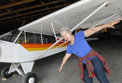 Susan Narehood of Beaver Springs demonstrates how her husband, Alan, would land their Piper Super Cub without flaps to slow the plane down Saturday April 21, 2012 during Snook Saturdays at Harold Snook's home and air strip in Beaver Springs.