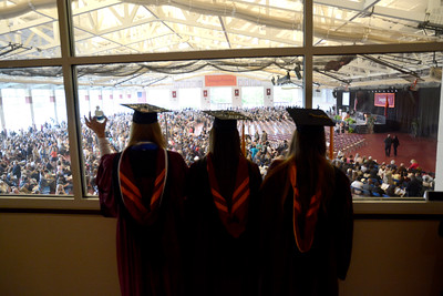 Susquehanna University graduates Shannon O'Connor, left, Marielle Fiorino, and Elizabeth Guy, look out over the crow gathered for Sunday's graduation at Susquehanna University.