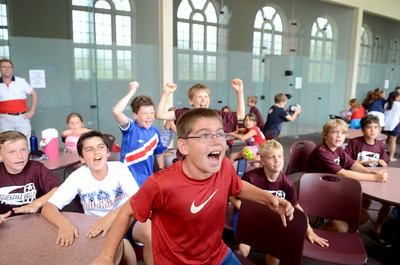 Josh Horst, 11, Mount Pleasant Mills, hops out of his seat as he cheers on the USA men's soccer team with his fellow campers at Susquehanna University, during the match against Germany on Thursday.