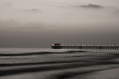 Evening at the Oceanside Pier, orange lights glowing at the beach. Light sepia tone. California.