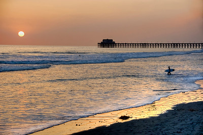 Surfer walking at the beach during beautiful sunset at the Oceanside Pier. California, USA.