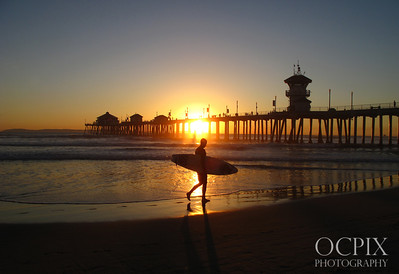 Surfer walks on beach at sunset
