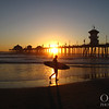 Surfer silhouette at sunset in Huntington Beach.