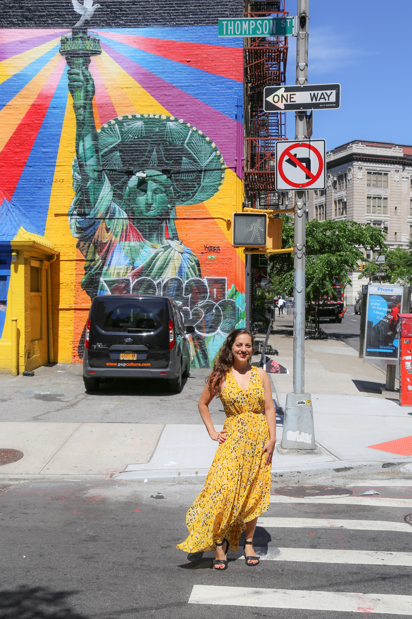 Kate in a yellow dress in front of a Statue of Liberty mural in SoHo, NYC