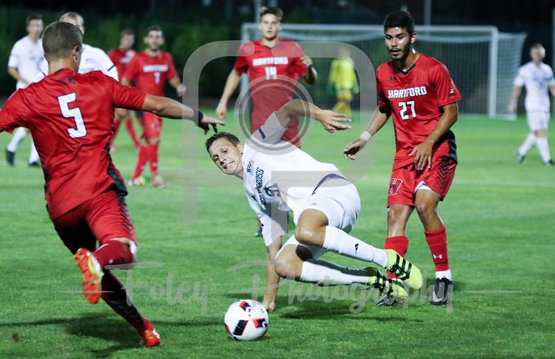 Hartford defender/midfielder Mike Barry (5) Holy Cross Crusaders forward Arno Rupp (9)