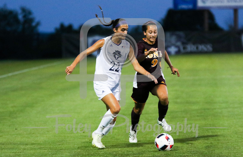Friday, August 19, 2016; Worcester, Massachusetts;  Holy Cross Crusaders forward Christina Napolitano (22) looks to make a play with pressure from Iona Gaels forward Marisa Bentley (9) during the Crusaders 3-1 victory.