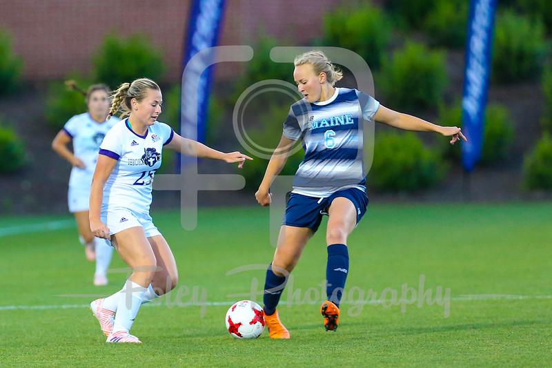 Holy Cross Christina Callahan (25) Maine midfielder Emilie Andersen (6)