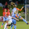 Washington Spirit midfielder Tori Huster holds back two Dash players from winning the ball after a split header.