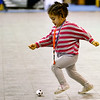 Youngster dribbling a small soccer ball at a youth clinic.