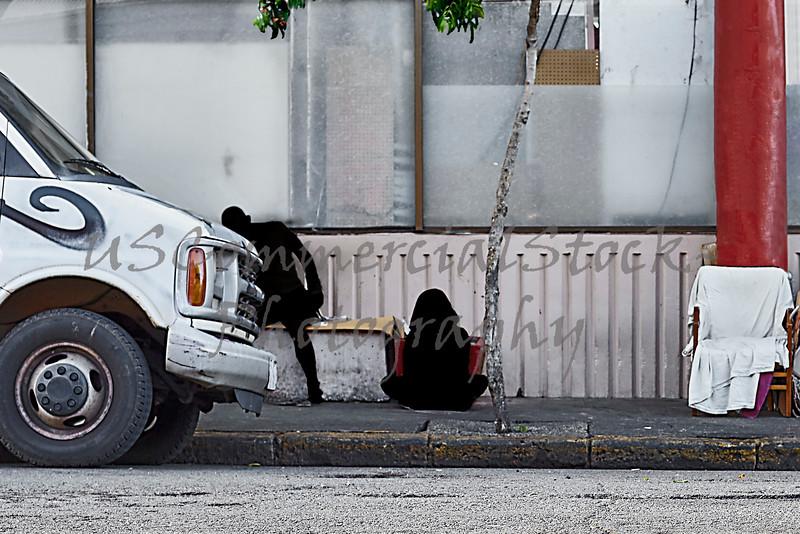 Homeless shadow figures inner city sidewalk