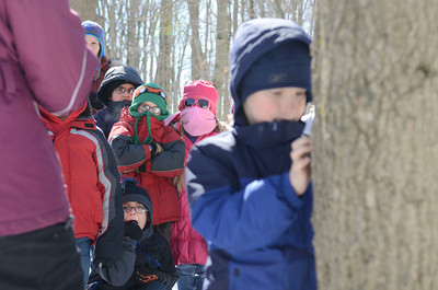 Second grade students from Kelly Elementary try to stay warm as their classmate Evan Gill, right, looks for a spot to tap a maple tree on Friday during a class field trip to the PPL Montour Preserve.