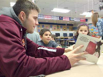 Susquehanna University men's basketball player Jake Wiles, left, reads to Selinsgrove kindergarten students Jonathen Kambhampati, 6, and Erica Boyer, 5, on Wednesday afternoon.