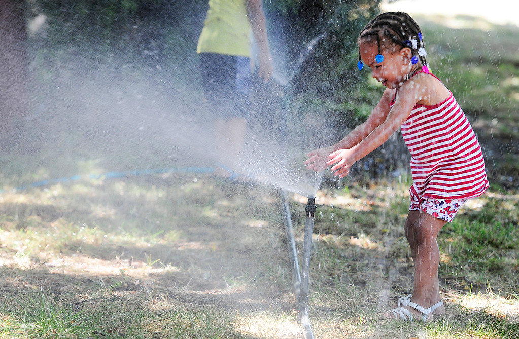 . VALLEJO, CA - JUNE 30, Miracle Maddox, 2, cools off in a spinkler at the Solano County Fair on Saturday. (CHRIS RILEY/TIMES-HERALD)