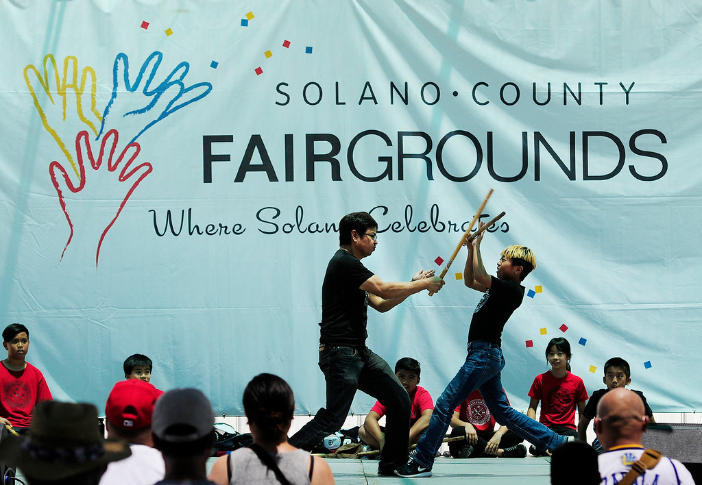 . VALLEJO, CA - JUNE 30, Jared Bergonia, of Benicia, defends a strike from his dad Julius during a demonstration on the Cultural Stage by Island Warrior Martial Arts on the first day of the Solano County Fair in Vallejo.(CHRIS RILEY/TIMES-HERALD)