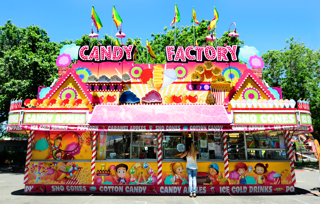 . VALLEJO, CA - JUNE 30, A woman orders food from the brightly colored Candy Factory at the Solano County Fair on Saturday. (CHRIS RILEY/TIMES-HERALD)