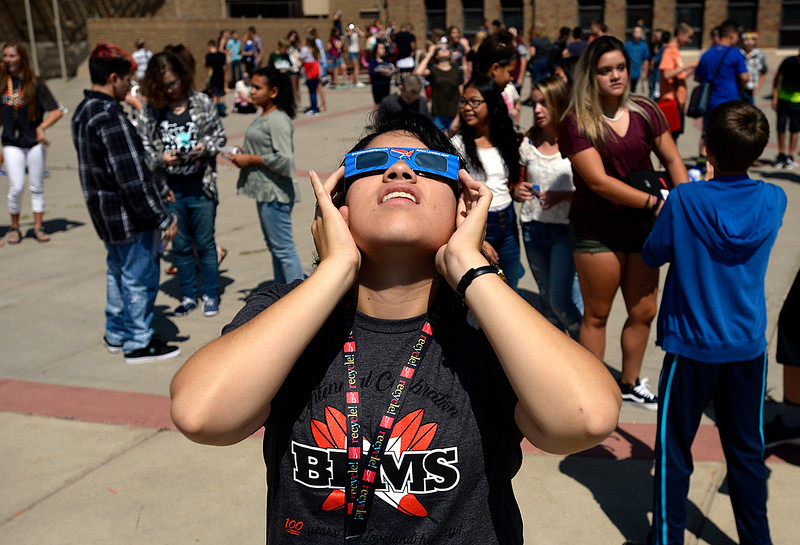 Bill Reed Middle School band teacher Alex Chavez watches the solar eclipse through protective glasses Monday, Aug. 21, 2017, from the courtyard at the school in downtown Loveland.  (Photo by Jenny Sparks/Loveland Reporter-Herald)