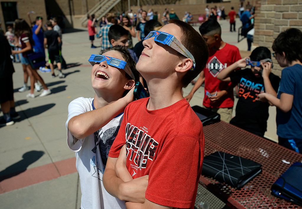 . Bill Reed Middle School seventh-graders Devon McNear, 12, left, and Jackson McCarthy, 12, right, react as they watch the solar eclipse through protective glasses Monday, Aug. 21, 2017, from the courtyard at the school in downtown Loveland.  (Photo by Jenny Sparks/Loveland Reporter-Herald)