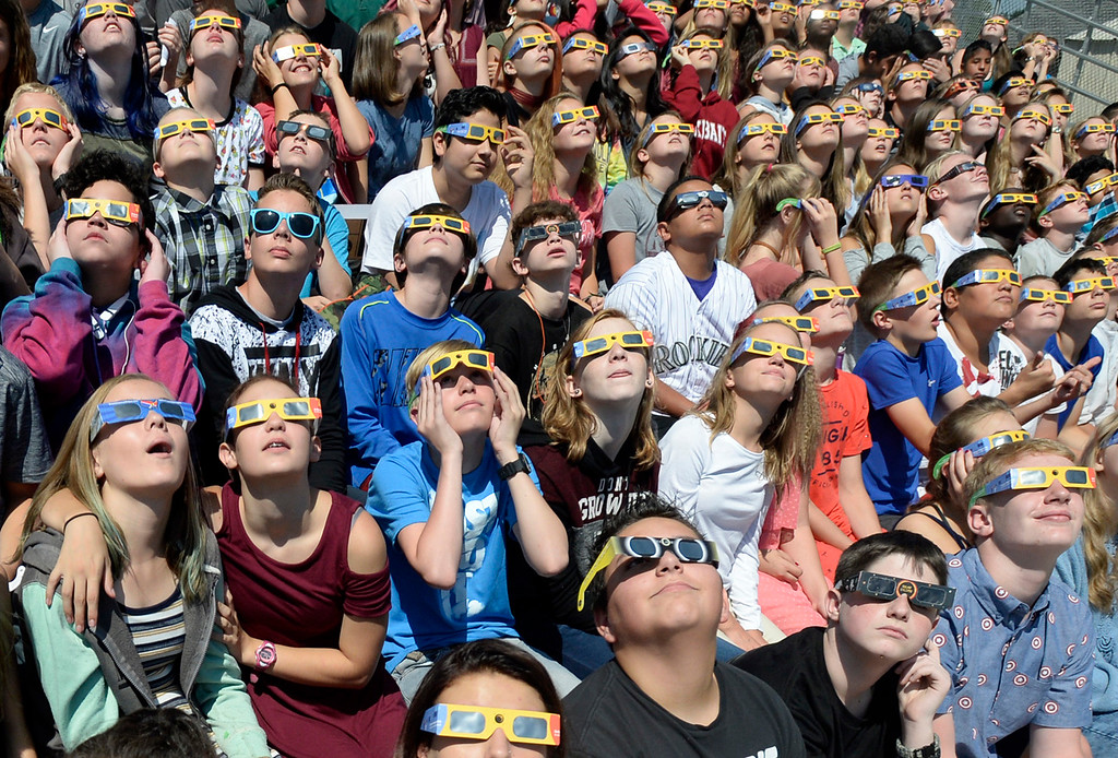 . Bill Reed Middle School students, including from left in the front row, Summer Thompson, 13, Ethan Wilson, 13, Aidan Williams, 14, and Ben Burleson, 13,  watch the solar eclipse through protective glasses Monday, Aug. 21, 2017, from the bleachers at the school in downtown Loveland.  (Photo by Jenny Sparks/Loveland Reporter-Herald)