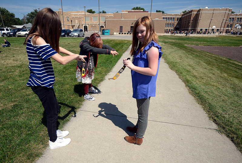 Bill Reed Middle School students Leanne Cotton, 11, left, Nija Anguiano, 11, center, and Bryce Coble, 11, cast shadows on the ground while gathering outside to watch the solar eclipse through protective glasses Monday, Aug. 21, 2017, at the school in downtown Loveland.  (Photo by Jenny Sparks/Loveland Reporter-Herald)