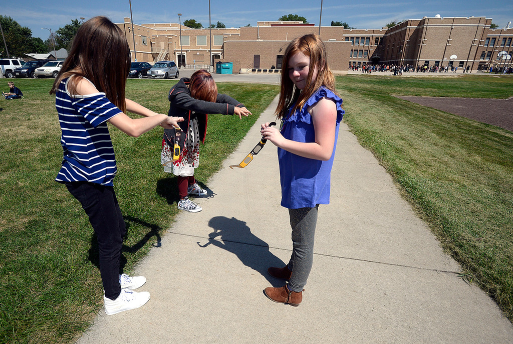 . Bill Reed Middle School students Leanne Cotton, 11, left, Nija Anguiano, 11, center, and Bryce Coble, 11, cast shadows on the ground while gathering outside to watch the solar eclipse through protective glasses Monday, Aug. 21, 2017, at the school in downtown Loveland.  (Photo by Jenny Sparks/Loveland Reporter-Herald)
