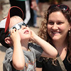 Four-yr-old Zander Cherry takes a peek at the solar eclipse while mom Amanda looks on.