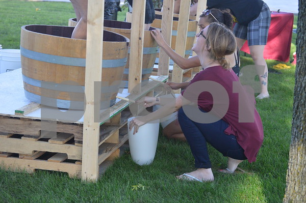 Katie Conell helps her stomping partner get as much juice from the barrel as possible.
