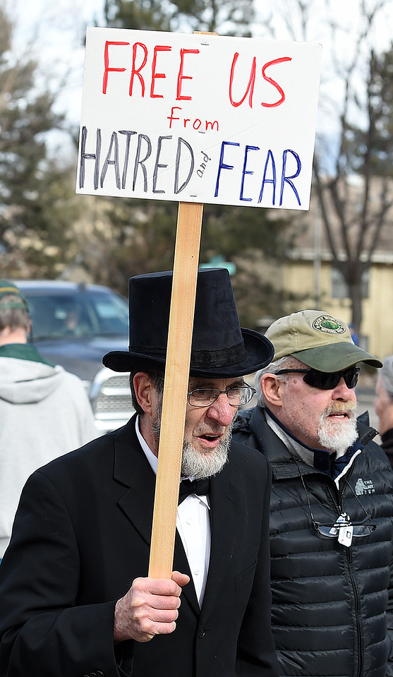 Dressed as Abraham Lincoln, John Brisbee marches with others during the Marching in Solidarity with Our Immigrant and Muslim Neighbors event Tuesday, Jan. 31, 2017, on Sheilds Street and Rolland Moore Drive in Fort Collins.   (Photo by Jenny Sparks/Loveland Reporter-Herald)