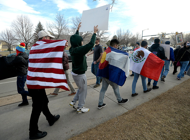 Colorado State University students march wearing the American flag, the Colorado flag, and the Mexican flag during the Marching in Solidarity with Our Immigrant and Muslim Neighbors event Tuesday, Jan. 31, 2017, on Sheilds Street and Rolland Moore Drive in Fort Collins. From left are Ivan Omar, Miguel DeJesus, Alonso Chavez Gasca, Ivan Loya, and Alan Perez.  (Photo by Jenny Sparks/Loveland Reporter-Herald)