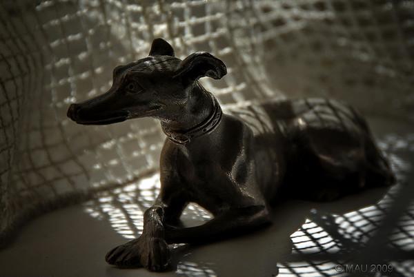 """Este perro de bronce, de unos 12 cm de largo, lleva años ahí sentado y en la misma postura, en la ventana del comedor. Sin embargo, no fue hasta hace un par de días que """"vi la foto"""". Quizá debido a la luz del momento y mi nueva 'mentalidad' desarrollada últimamente. En el post-proceso he oscurecido un poco las esquinas con un sutil 'viñeteo'.<br /> <br /> This bronze dog, about 12 cm long, has been there for years sitting on the dining room window. But it wasn't till a couple of days ago that I """"saw the photo"""". Perhaps due to the light at that moment and to my """"new mentality"""" developed lately. In post-processing I darkened a bit the corners with a subtle vignetting."""